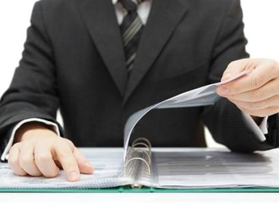 an accountant examines a trial balance sheet