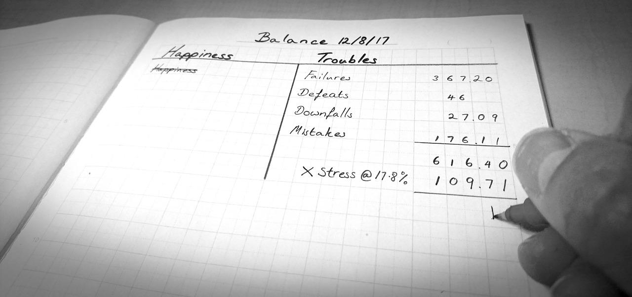 a hand holding a pen filling out a balance sheet