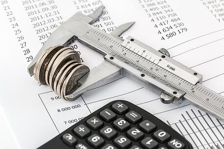 a calculator, ruler, coins, and balance sheet used to calculate small-business expenses